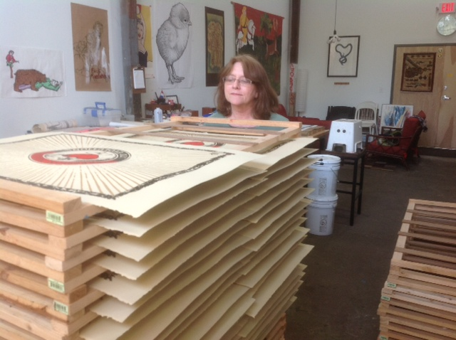 "Margete Griffin inspects prints for the ""Hero or Non-Hero?"" series."